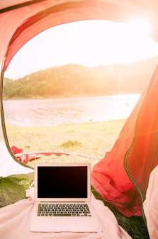 Laptop, der draußen im zelt steht