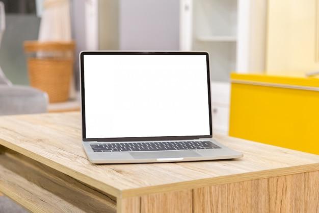 Laptop, der leeren bildschirm auf vorderansicht der arbeitstabelle im haus zeigt