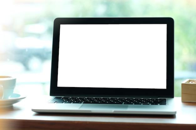 Laptop des leeren bildschirms auf hölzerner tabelle durch fensterhintergrund, geschäft und technologiekonzept.