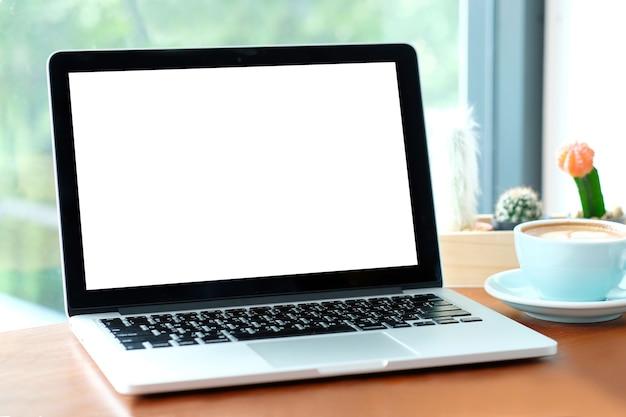 Laptop des leeren bildschirms auf hölzerner tabelle mit fensterhintergrund.