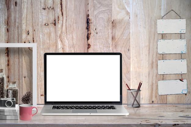 Laptop des leeren bildschirms des modells auf holztisch mit versorgungen.