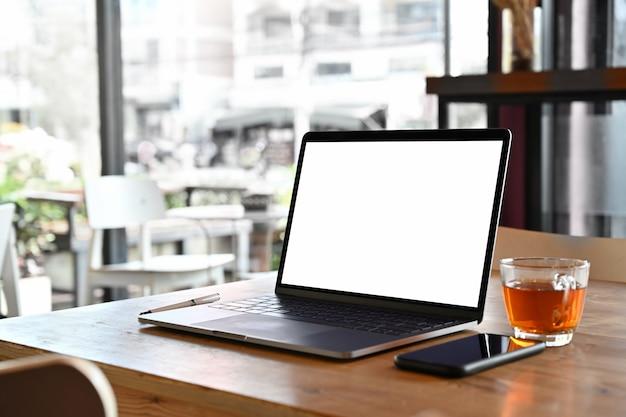 Laptop des leeren bildschirms des modells auf tabelle im caféhintergrund.