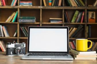 Laptop des leeren Bildschirms mit Retro- Kamera; gelbe Kaffeetasse; Buch auf Tisch im Bibliotheksraum gestapelt