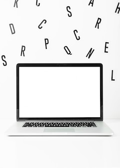 Laptop des leeren bildschirms mit zerstreuten alphabeten auf weißem hintergrund