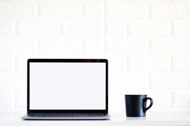 Laptop des leeren bildschirms und eine schale schwarzer kaffee auf weißem backsteinmauerhintergrund