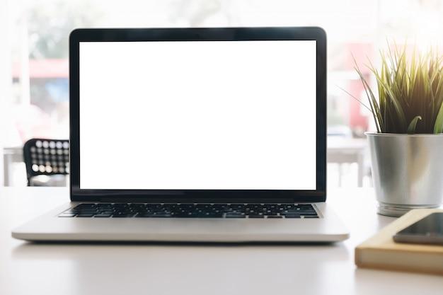 Laptop des modells des leeren bildschirms auf schreibtisch im büroraumhintergrund.