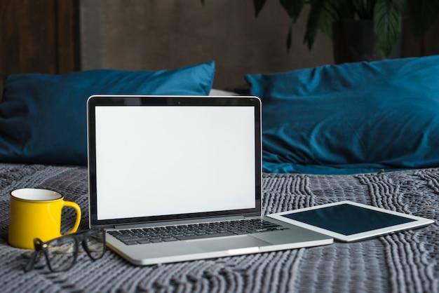 Laptop; digitales tablett; brille und tasse auf dem bett