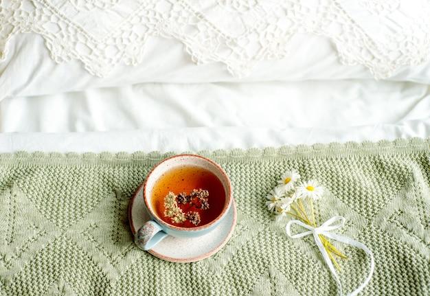 Laptop, eine tasse tee, weißes bett und plaid. sonniger morgen und frühstück. online arbeiten in einem komfortablen zuhause. gemütliches helles zimmer.