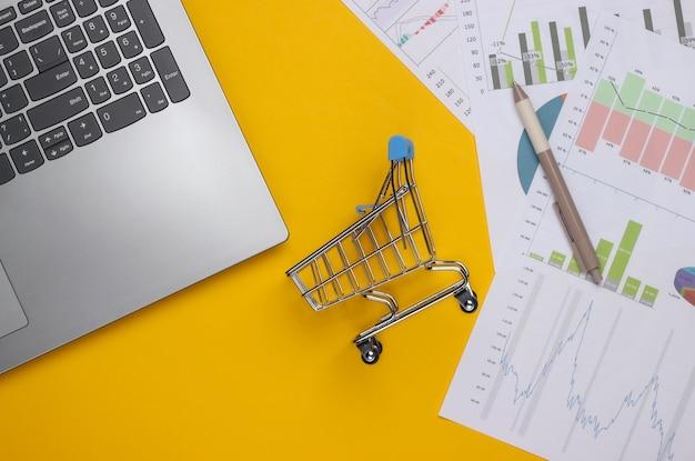 Laptop, einkaufswagen mit grafiken und diagrammen auf gelbem grund. geschäftsplan, finanzanalyse, statistik. draufsicht