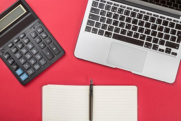 Laptop, füllfederhalter, rechner und notizbuch auf rot