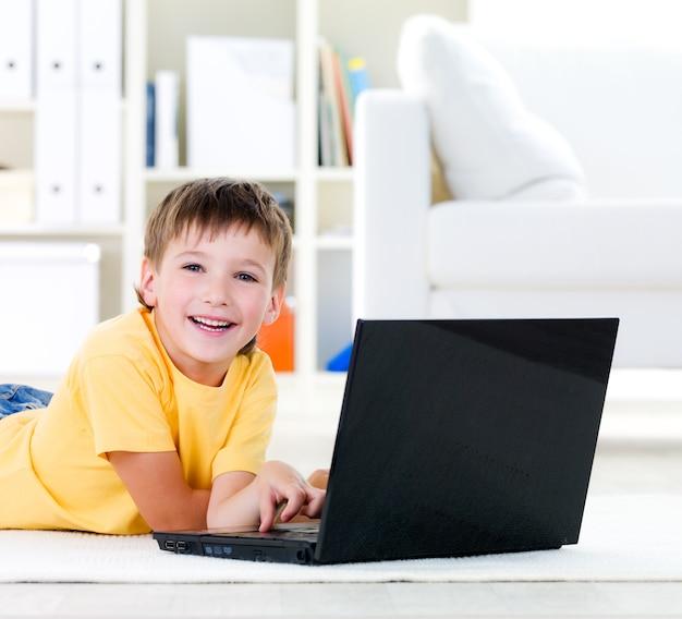 Laptop für glücklichen kleinen jungen, der zu hause auf dem boden liegt - drinnen