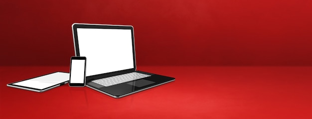Laptop, handy und digitaler tablet-pc auf rotem schreibtisch