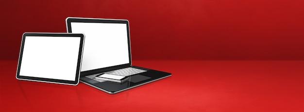Laptop, handy und digitaler tablet-pc auf rotem schreibtisch.