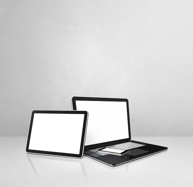 Laptop, handy und digitaler tablet-pc auf weißem betonschreibtisch. 3d-illustration