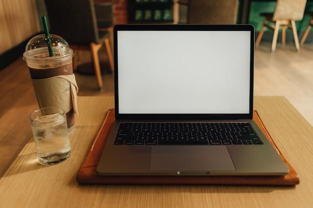 Laptop im kaffeecafé mit weißer leerer anzeige.