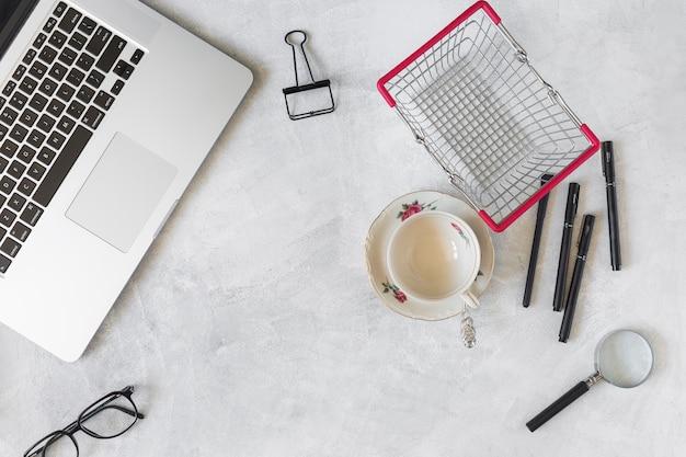 Laptop in der nähe von briefpapier und supermarktkorb