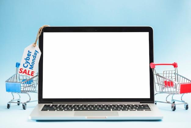 Laptop in der nähe von einkaufswagen und tag