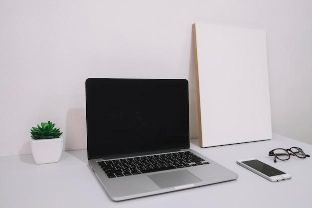 Laptop in der nähe von leeren poster