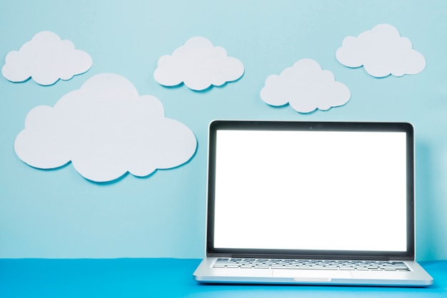 Laptop in der nähe von papier wolken