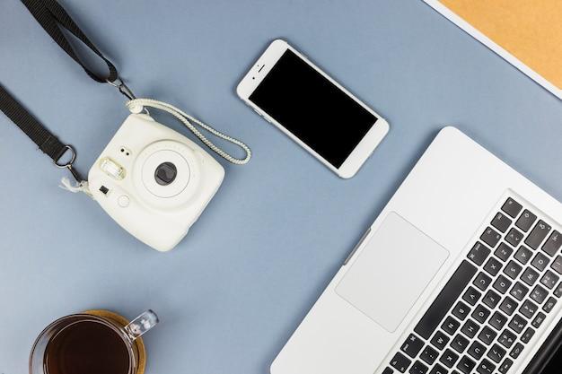Laptop in der nähe von smartphone, kamera und tasse getränk
