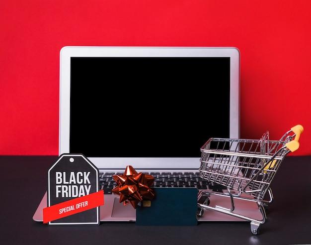 Laptop in der nähe von spielzeug zeichen, kreditkarte und supermarkt warenkorb