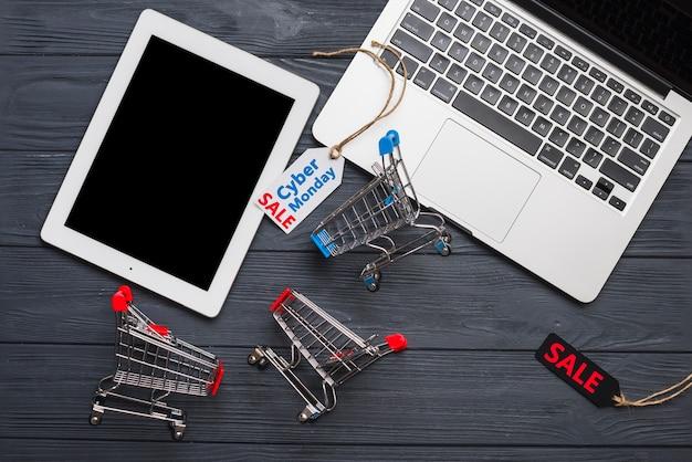 Laptop in der nähe von tags, tablet und supermarkt-wagen