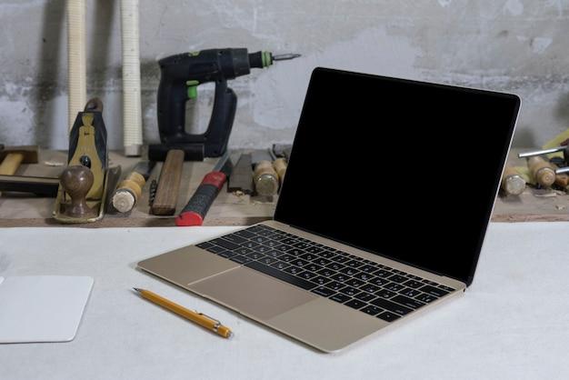 Laptop in einer zimmereiwerkstatt auf einem werktisch, werkzeugen und einem bohrgerät im hintergrund