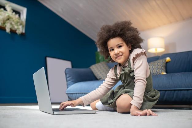 Laptop, interesse. glückliches kleines dunkelhäutiges mädchen mit laptop, das zu hause auf dem boden sitzt und die tastatur mit der hand berührt