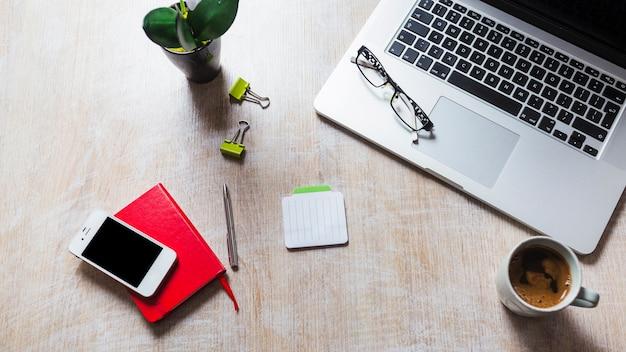Laptop mit brille; schreibwaren; handy; kaffeetasse auf dem tisch