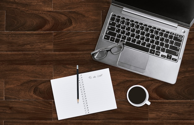 Laptop mit brillen und notizbuch mit, zum der liste auf hölzernem schreibtisch mit kopienraum zu tun.