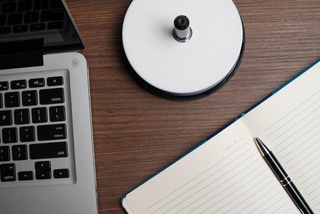 Laptop mit cd und notizbuch mit stift