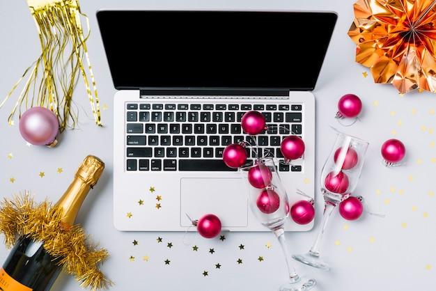 Laptop mit champagnerflasche auf weißer tabelle