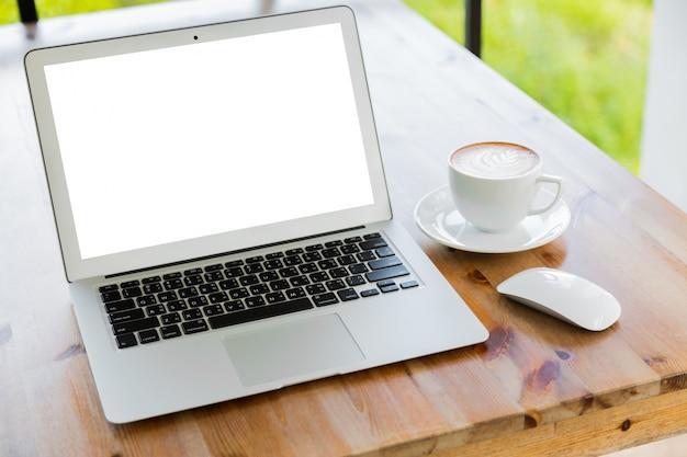 Laptop mit einer tasse kaffee neben