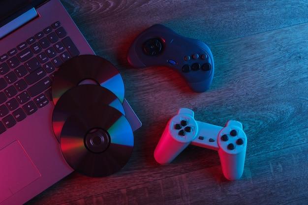 Laptop mit gamepads, cd-discs auf holzboden