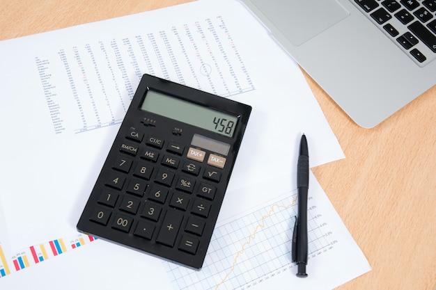 Laptop mit geschäftsdiagrammen und taschenrechner auf dem schreibtisch