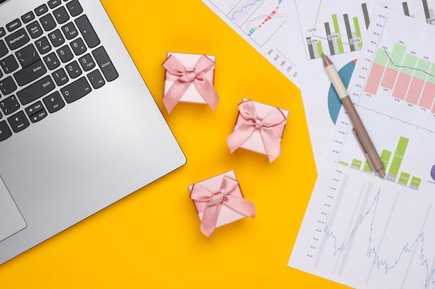 Laptop mit geschenkboxen, grafiken und diagrammen auf gelbem hintergrund. geschäftsplan, finanzanalyse, statistik. draufsicht