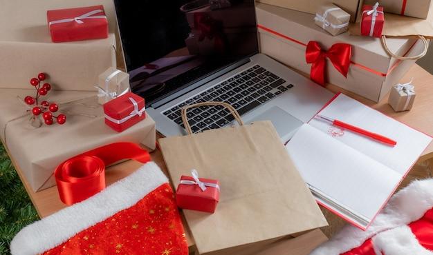 Laptop mit geschenken, verpackungsboxen und einkaufstasche am arbeitsplatz, lieferkonzept.