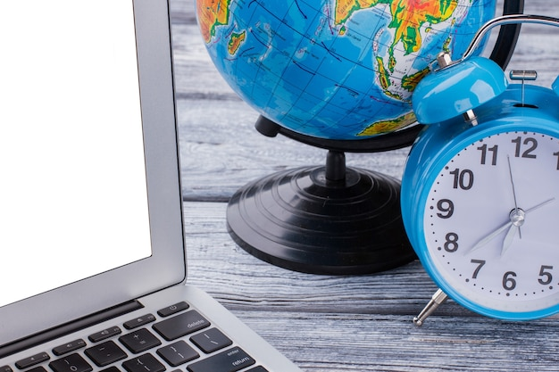 Laptop mit globalisierungs- und zeitkonzept. schließen sie den offenen laptop mit wecker und erdkugel auf einem weißen holztisch.