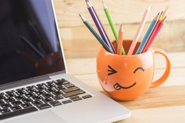 Laptop mit glücklichem gesichtsbecher der smileyfalte für digitales künstlerkonzept der idee.