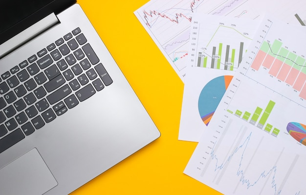 Laptop mit grafiken und diagrammen auf gelbem grund. geschäftsplan, finanzanalyse, statistik. draufsicht