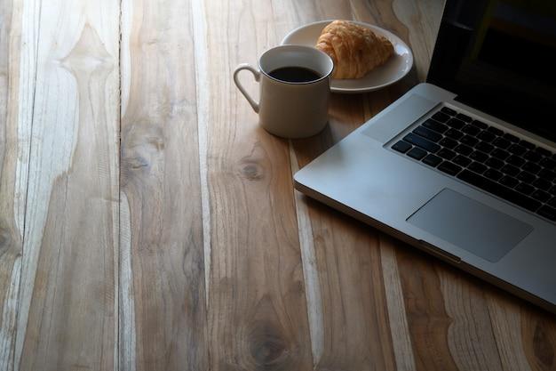 Laptop mit kaffee auf hölzernem arbeitsplatz und kopienraum