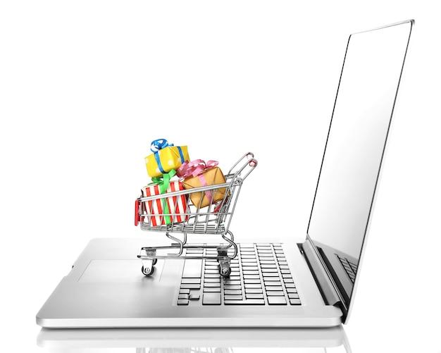 Laptop mit kleinem einkaufswagen voller geschenke isoliert auf weißer oberfläche
