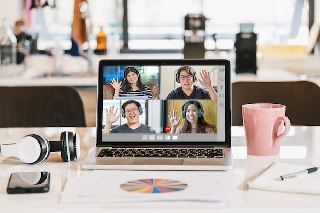 Laptop mit kopfhörer-kaffeetasse-handy und datendiagrammdokument, das asiatischen geschäftsmann zeigt