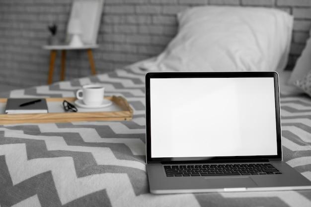 Laptop mit leerem bildschirm auf dem bett