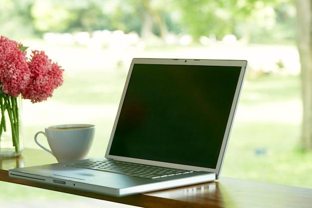 Laptop mit leerem bildschirm auf dem tisch zu hause