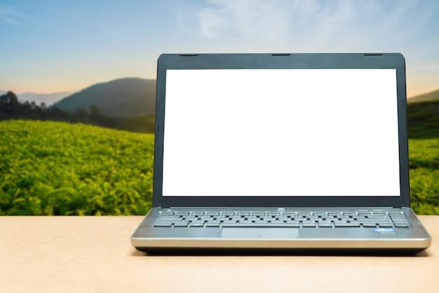 Laptop mit leerem bildschirm auf tabelle mit unschärfegrünnatur im hintergrund. technologiekonzept