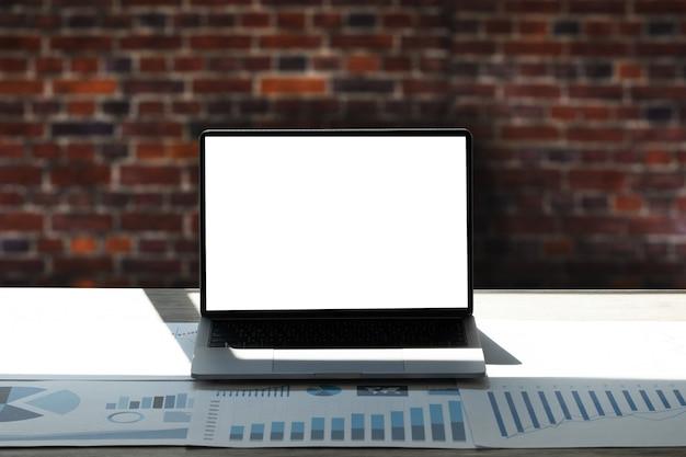 Laptop mit leerem bildschirm auf tischinnenraum, mann an seinem arbeitsplatz unter verwendung der technologie