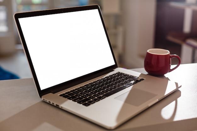 Laptop mit leerem bildschirm, hauptinnenraum oder büro