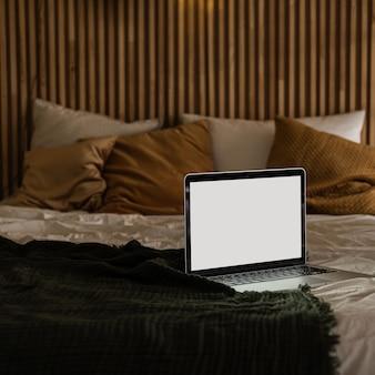 Laptop mit leerem bildschirm im bett mit kissen und bettwäsche. moderne innenarchitektur im minimalistischen stil.