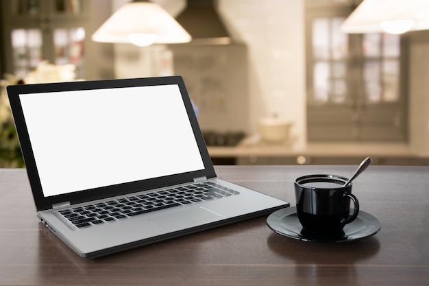 Laptop mit leerem bildschirm mit kaffee auf tischplatte. zuhause arbeiten. kaffeepause. bildung. e-learning.